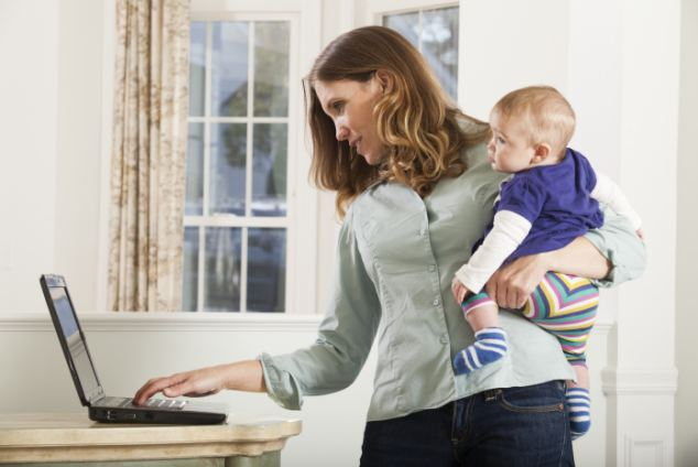 Woman working on a computer at home while holding baby